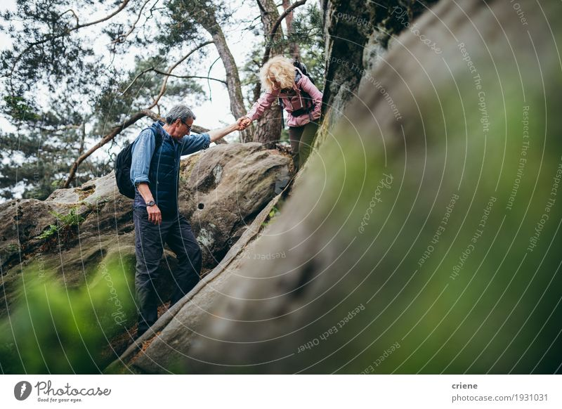 Fit Caucasian Senior couple hiking on rocks in forest Human being Woman Man Relaxation Clouds Joy Forest Mountain Adults Sports Couple Rock Leisure and hobbies Hiking Action 45 - 60 years