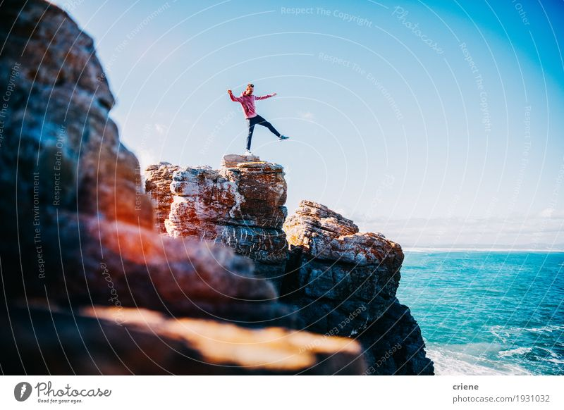Young happy man balancing on cliff at the ocean Human being Vacation & Travel Youth (Young adults) Blue Young man Ocean Joy Lifestyle Coast Happy Freedom Rock Bright Masculine Trip Waves