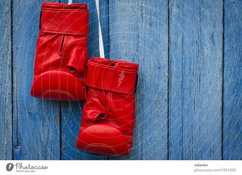 Red leather boxing gloves hanging on a rope Old Blue Sports Wood Dirty Retro Success Might Symbols and metaphors Ring Shabby Conceptual design Competition