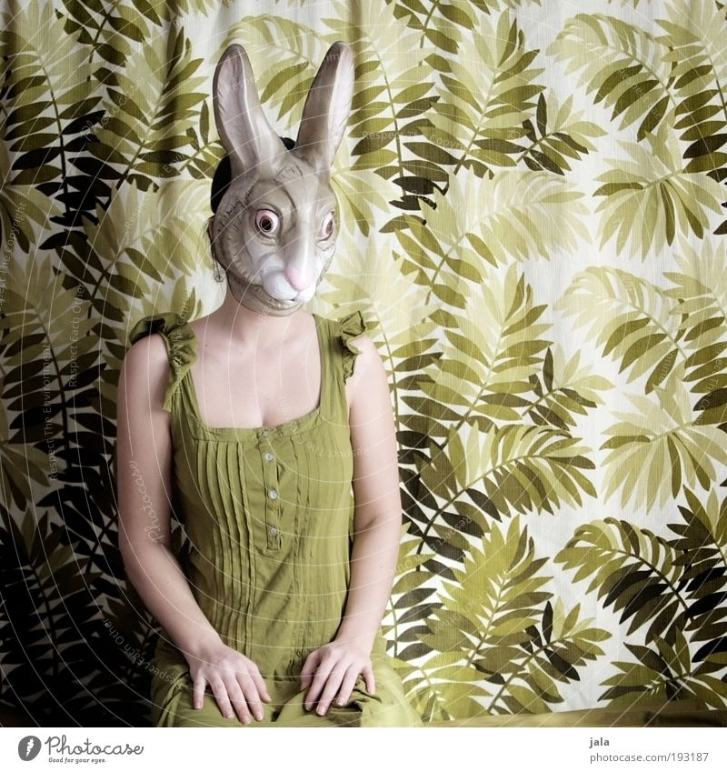 Apathetic sitting around Human being Feminine Woman Adults Sit Green Hare & Rabbit & Bunny Mask Easter Carnival costume Colour photo Interior shot Day