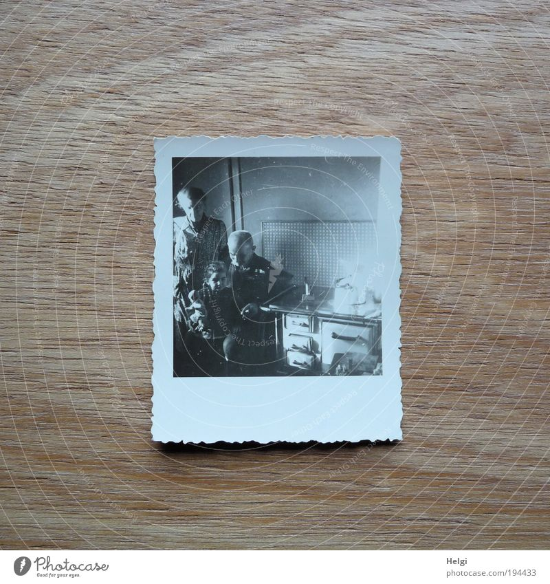 Photo of a photo in a historical kitchen with grandpa, mother, child and doll Human being Masculine Child Woman Adults Man Female senior Male senior Infancy
