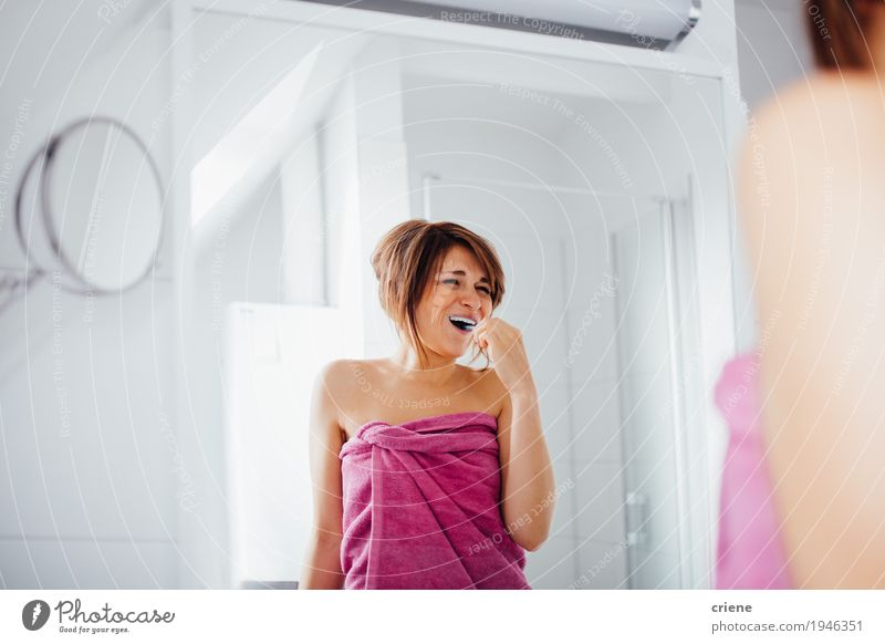 Happpy Young caucasian women brushing her teeth Lifestyle Joy Beautiful Personal hygiene Face Healthy Health care Well-being Living or residing Mirror Bathroom