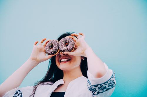 Caucasian women making funny face with chocolate donuts Human being Woman Youth (Young adults) Blue Young woman Joy Adults Eating Lifestyle Funny Feminine Food