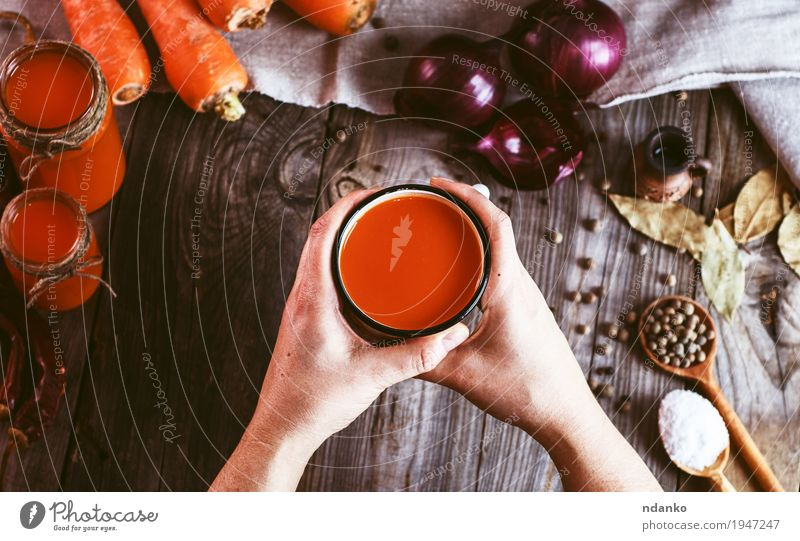 female hands holding an iron mug with carrot juice Human being Woman Youth (Young adults) Old Hand Red Leaf 18 - 30 years Adults Eating Wood Food Health care Gray Orange Fruit