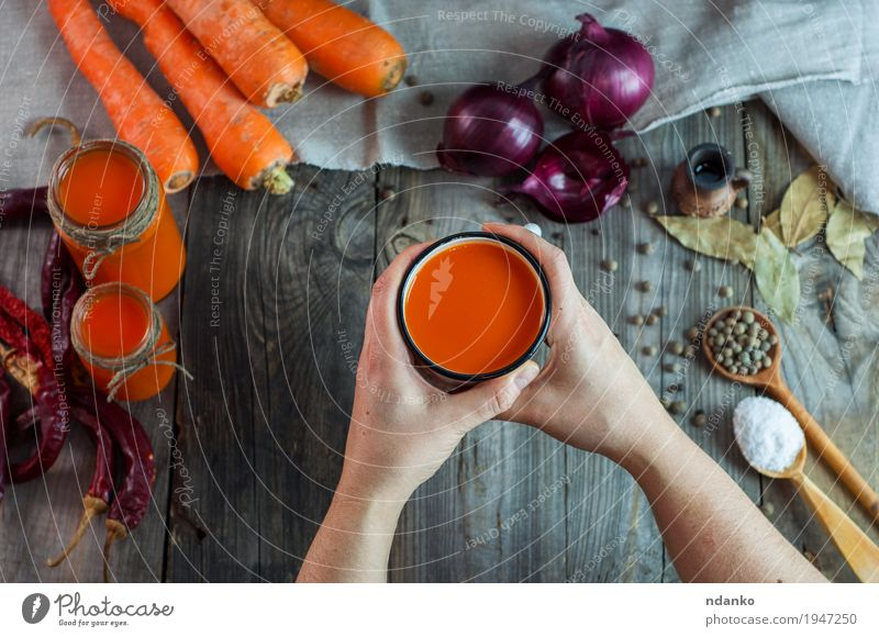female hands holding an iron mug with carrot juice Food Vegetable Herbs and spices Drinking Juice Cup Mug Spoon Body Table Young woman Youth (Young adults) Arm