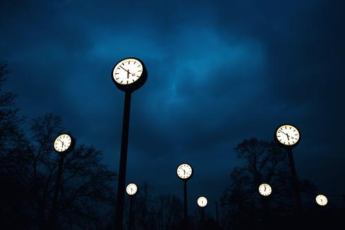 Many luminous watches in the Uhrenpark Düsseldorf at night Clock face time change Clouds Night sky Park Illuminate Exceptional Tall Blue Black White