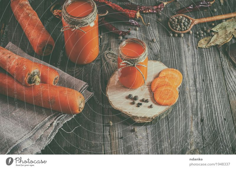 Fresh carrot juice with pulp among the vegetables and spices Nature Old Natural Wood Health care Gray Above Orange Nutrition Fresh Glass Table Rope Herbs and spices Beverage Kitchen
