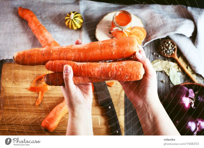 female human hand holding three large orange carrot Food Vegetable Herbs and spices Nutrition Vegetarian diet Diet Beverage Juice Table Kitchen Woman Adults