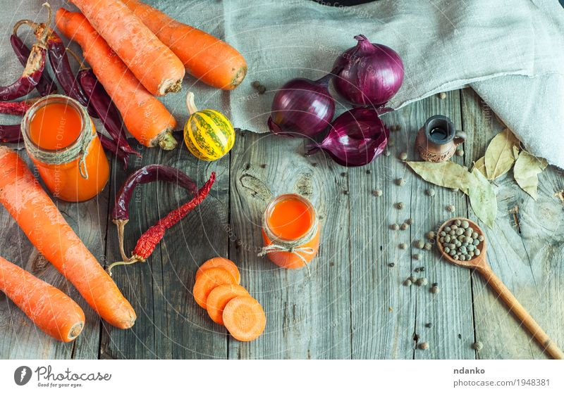 Fresh carrots and carrot juice in a glass container Vegetable Herbs and spices Vegetarian diet Diet Beverage Juice Glass Table Kitchen Nature Wood Old Eating