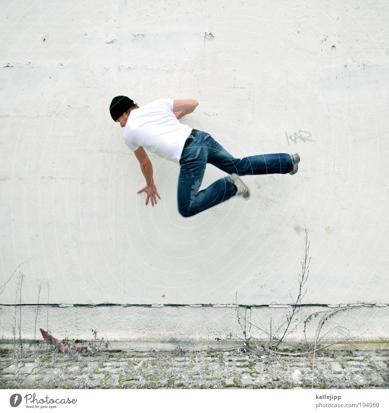 Human being Man Adults Wall (building) Playing Wall (barrier) Jump Power Footwear Facade Masculine Success T-shirt Jeans Cap Force