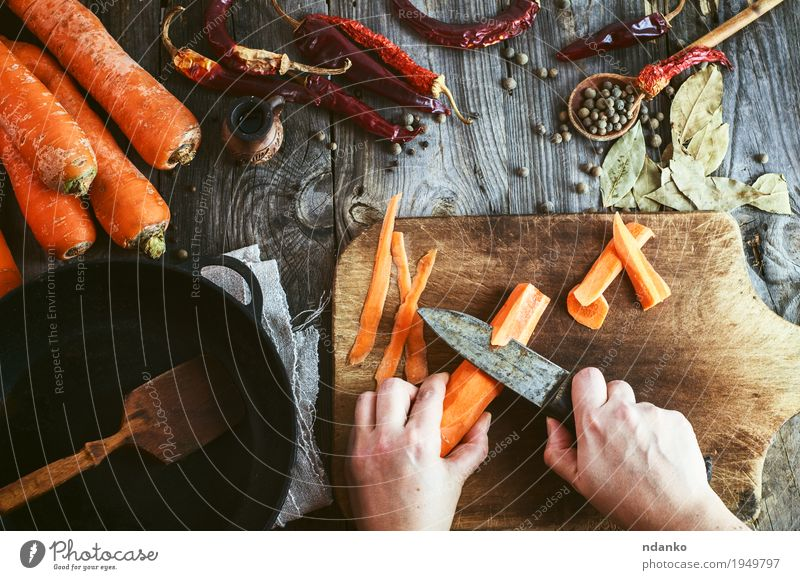 Two women's hands clean large carrots for slicing Food Vegetable Herbs and spices Nutrition Eating Vegetarian diet Crockery Pan Knives Spoon Table Young woman