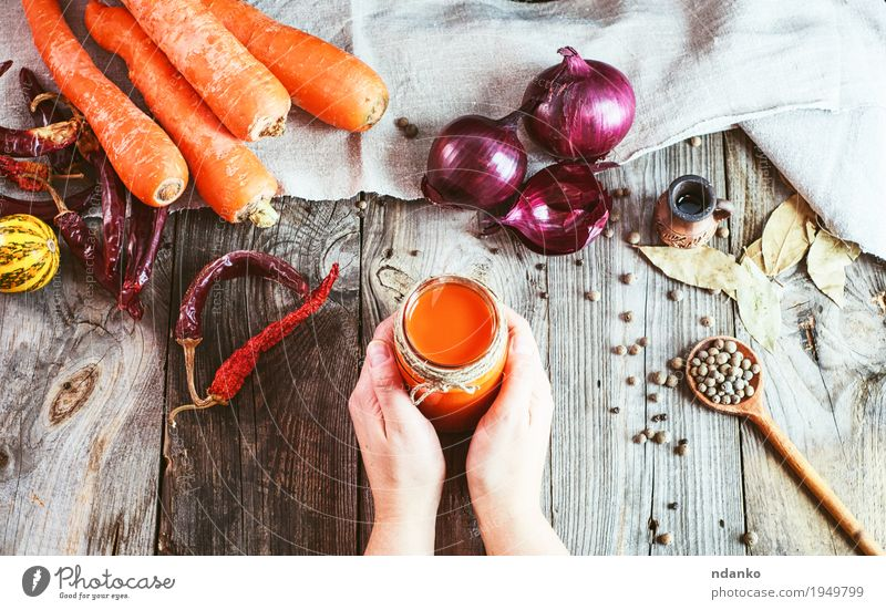female hands holding a jar with a glass of fresh carrot juice Human being Woman Youth (Young adults) Hand Red Leaf 18 - 30 years Adults Eating Natural Wood Health care Gray Above Orange Nutrition