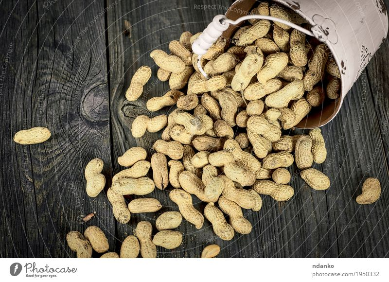 Spilling from white metal bucket of peanuts in the shell White Dish Yellow Wood Food Gray Above Bright Metal Table Vegetable Breakfast Bowl Meal Diet Conceptual design