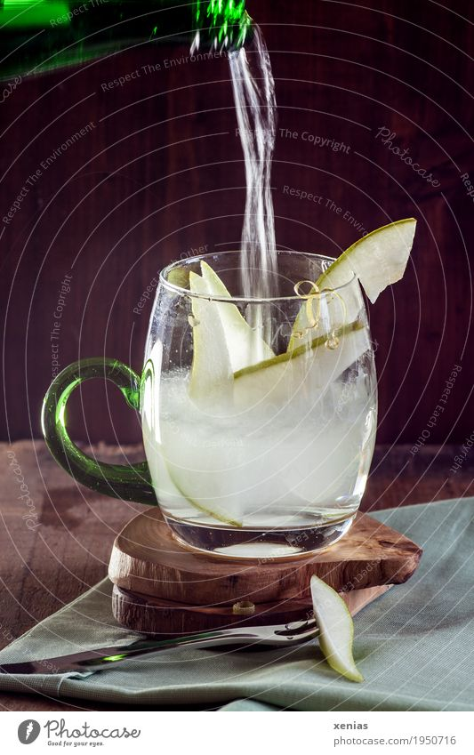 fresh pear water - mineral water pours into a glass with pear wedges against a dark background Pear Drinking water fruit Beverage Cold drink bottle Glass Fork