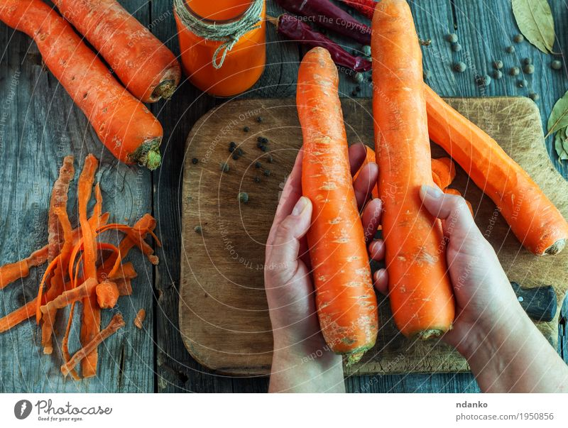 Two large ripe carrots lie in female hands Vegetable Nutrition Vegetarian diet Diet Beverage Juice Bottle Body Healthy Eating Table Woman Adults Hand Fingers 1