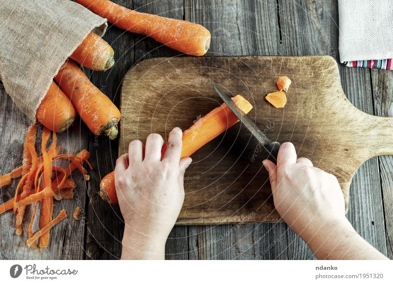 process of cutting slices of carrot on a kitchen board Food Vegetable Nutrition Vegetarian diet Diet Knives Body Healthy Eating Table Woman Adults Hand Fingers