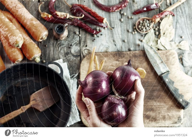 three large red onions in female hands Food Vegetable Herbs and spices Eating Vegetarian diet Pan Knives Spoon Table Cook Kitchen Woman Adults Hand Fingers