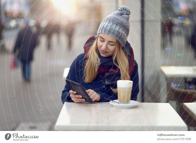 Young blond woman with mobile drinking coffee Woman Beautiful Winter Face Adults Street Lifestyle Happy Copy Space Blonde Sit Technology Table Smiling Reading