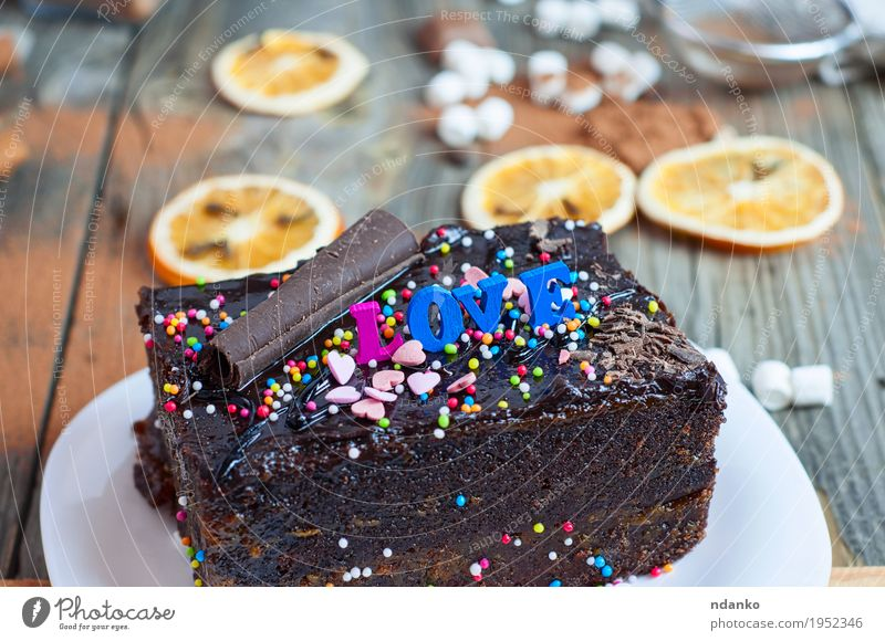 piece of chocolate cake Sacher with sweet grit and the word love White Emotions Love Wood Gray Feasts & Celebrations Brown Orange Fruit Decoration Table Shopping Delicious Restaurant Tradition Dessert