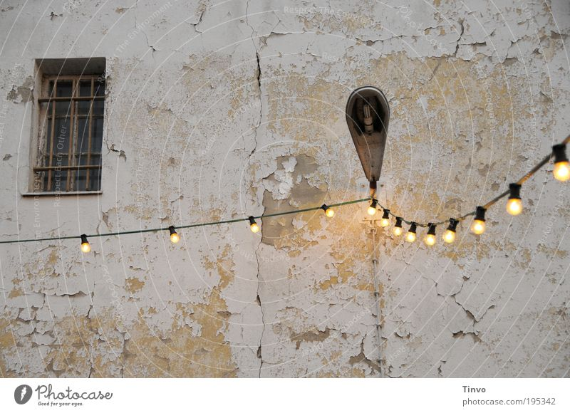Illuminated lamp Wall (barrier) Wall (building) Facade Window Old Dirty Fairy lights Electricity Electric bulb Lantern Exterior lighting latticed