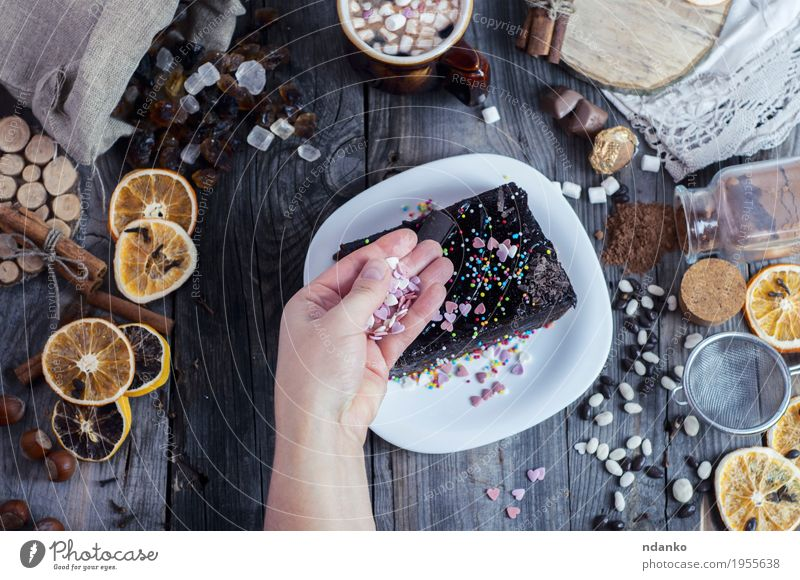 Female hand sprinkles sugar hearts piece of Sachertorte Woman Youth (Young adults) White Hand 18 - 30 years Adults Eating Wood Gray Brown Above Fruit Decoration Arm Table Beverage