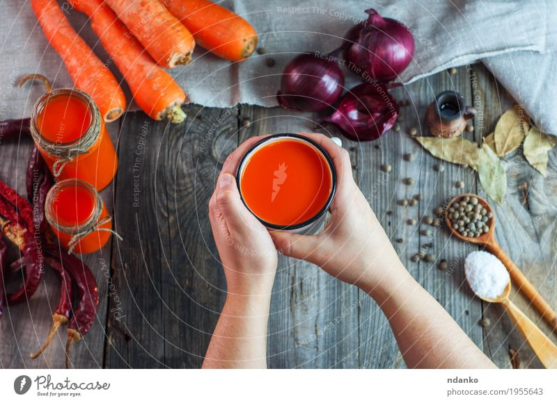 Iron mug with carrot juice in female hands Food Vegetable Herbs and spices Nutrition Beverage Cold drink Juice Cup Spoon Table Woman Adults Hand 1 Human being