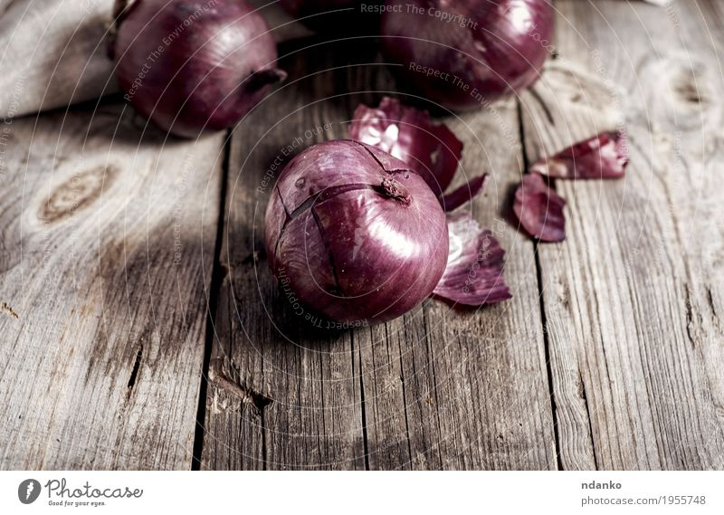 Red onions in the husk on the gray wooden surface Vegetable Vegetarian diet Plant Wood Old Dark Fresh Brown Onion ripe bulb Organic Salad Culinary Purple