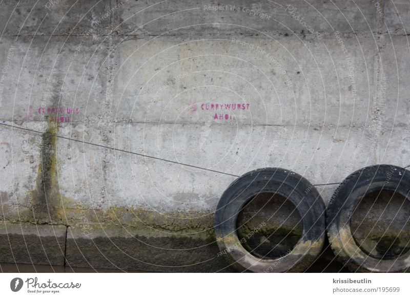 Currywurst I Wall (barrier) Wall (building) Car tire Tire harbour wall Stone Concrete Graffiti Discover Vacation & Travel Dirty Funny Gloomy Gray Pink Puzzle