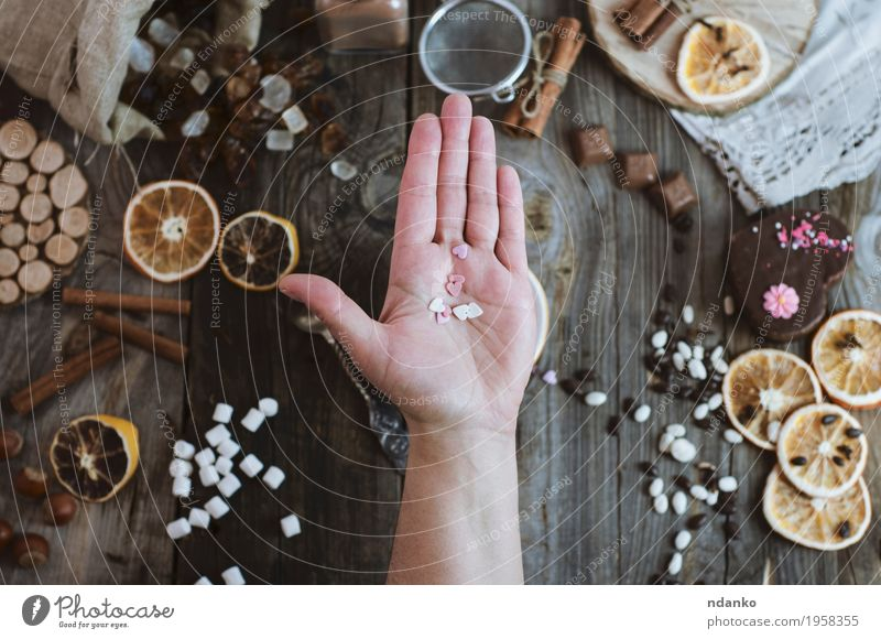 Open human palm on the background of the table with sweets Human being Woman Youth (Young adults) White Hand 18 - 30 years Adults Eating Wood Gray Brown Above Orange Fruit Decoration Open