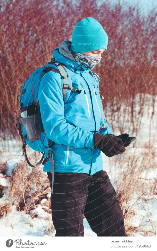 Boy using the mobile phone during the winter trip Lifestyle Joy Vacation & Travel Trip Adventure Freedom Expedition Winter Snow Winter vacation Hiking Sports