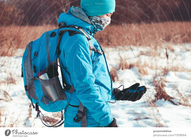 Boy using the mobile phone during the winter trip Lifestyle Joy Vacation & Travel Trip Freedom Winter Snow Winter vacation Sports Hiking Cellphone Technology