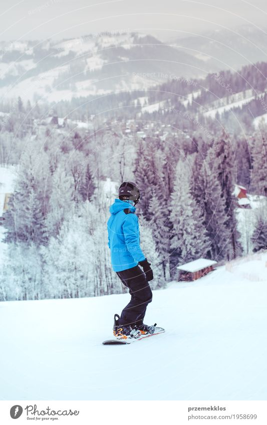Boy riding a snowboard down the slope Lifestyle Joy Vacation & Travel Winter Snow Winter vacation Mountain Sports Snowboard Boy (child) Nature Landscape Hill