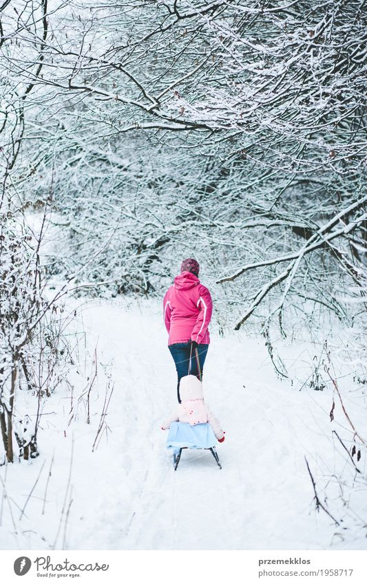 Woman pulling sledge with her little daughter Lifestyle Joy Trip Winter Snow Winter vacation Child Human being Baby Girl Adults Parents Mother