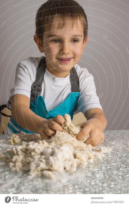 Little boy is kneading raw pizza dough and smiling Child Blue Joy Boy (child) Playing Smiling Kitchen Make Bread Delightful Baked goods Dough Raw Cookie Flour