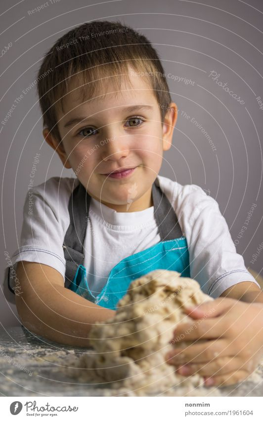 Little boy is kneading raw pizza dough and smiling Dough Baked goods Bread Joy Kitchen Child Boy (child) Infancy Smiling Make Blue Innocent Delightful Apron