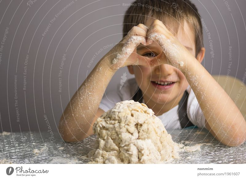 Boy is kneading raw dough looking through heart shape hands Dough Baked goods Bread Joy Playing Kitchen Child Boy (child) Infancy Hand Heart Smiling Make
