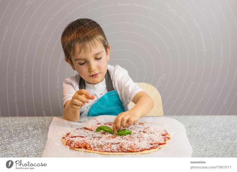 Little boy is making pizza, finishing with basil leafs Cheese Dough Baked goods Bowl Beautiful Leisure and hobbies Kitchen Child School Boy (child) Infancy Hand