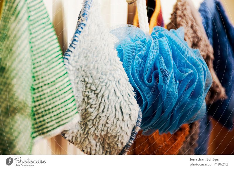 colourful washcloths hang in a row from the heating in the bathroom Blue Green Red White Floor cloth Hang up Clean Row Cloth Grading Shadow Light Contrast