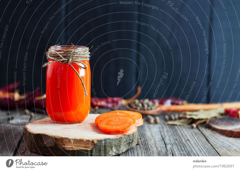 Jar of fresh carrot juice on a wooden surface Nature Healthy Eating Eating Autumn Natural Wood Gray Orange Nutrition Fresh Table Herbs and spices Beverage Delicious Vegetable Bottle
