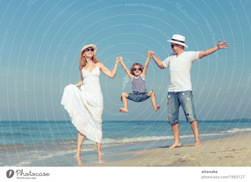 Happy family walking on the beach at the day time. Lifestyle Joy Relaxation Leisure and hobbies Playing Vacation & Travel Trip Freedom Summer Sun Beach Ocean