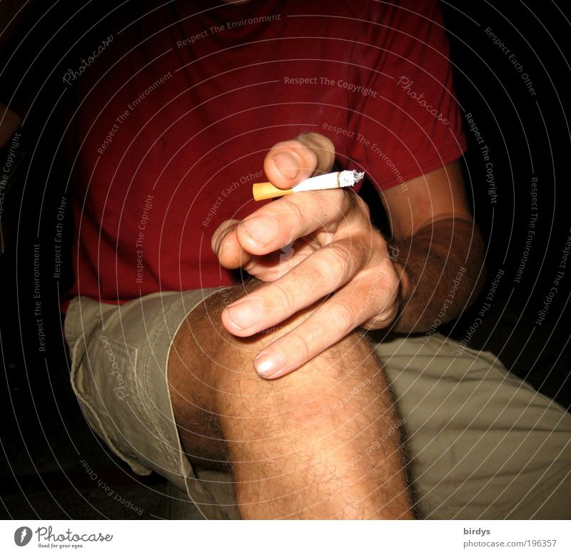 sitting man with short pants and burning cigarette in his hand Masculine Man Adults by hand Fingers Legs 1 Human being T-shirt Smoking Red Vice nervousness