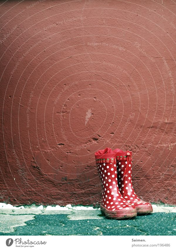 childhood memories Boots Rubber boots Joy Point Wall (building) Memory Infancy Childlike Stand Mud Experience Red Spotted Pattern Colour photo Exterior shot