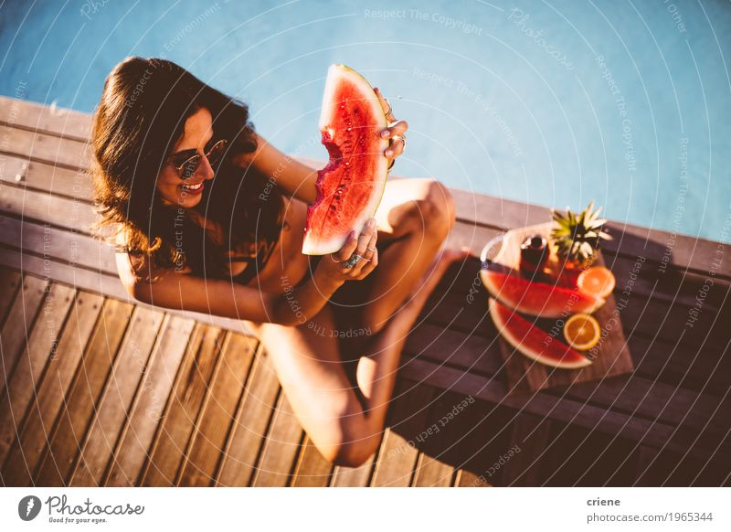 Young beautiful women in bikini sitting at swimming pool Woman Youth (Young adults) Summer Young woman Joy Adults Warmth Eating Lifestyle Feminine Swimming & Bathing Fruit Orange Happiness Smiling Swimming pool