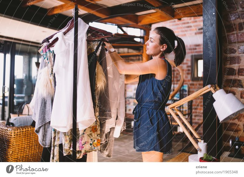 Young female designer hanging dresses on clothes rail Human being Youth (Young adults) Young woman Joy 18 - 30 years Adults Feminine Art Business Fashion Work and employment Office Modern Smiling Clothing Dress