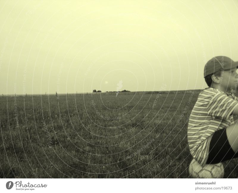 the waiting Boredom Panorama (View) Man Wait Ball Moon Evening Boy (child) Large Foot ball Striped Profile Baseball cap Meadow Pasture Nature Meditative