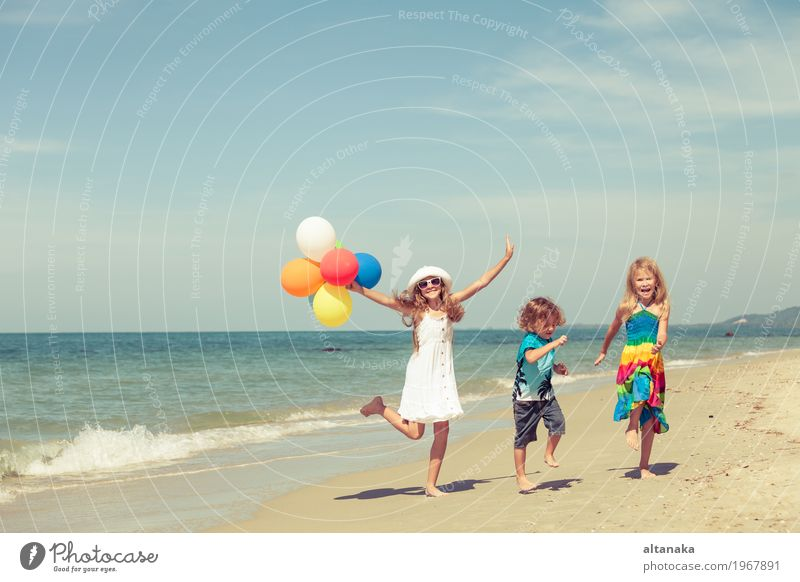 Three happy children with balloons dancing on the beach Human being Child Nature Vacation & Travel Summer Beautiful Sun Hand Ocean Relaxation Joy Girl Beach