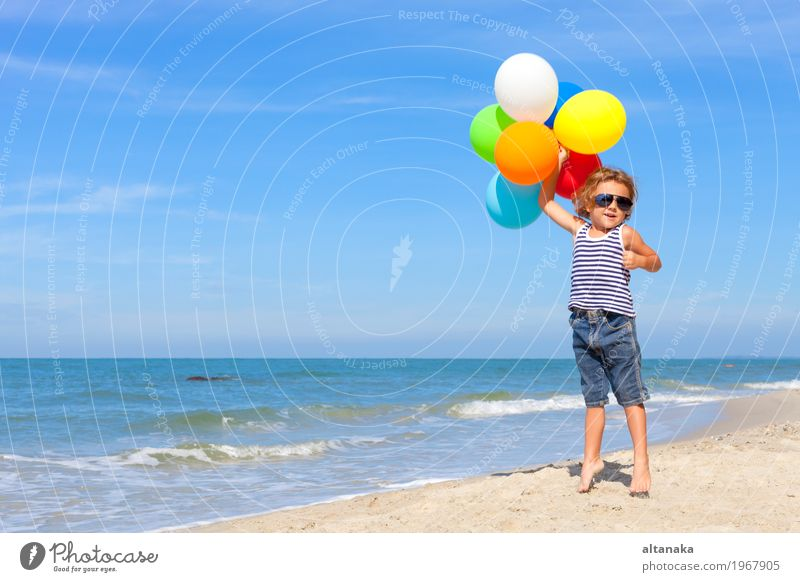 Little boy with balloons standing on the beach Human being Child Nature Vacation & Travel Man Summer Sun Hand Ocean Relaxation Joy Beach Adults Lifestyle