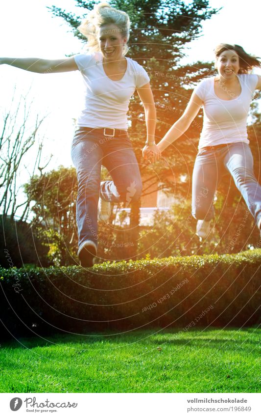 off through the hedge Human being Feminine Young woman Youth (Young adults) Friendship Adults 2 18 - 30 years Environment Nature Sunlight Spring Laughter
