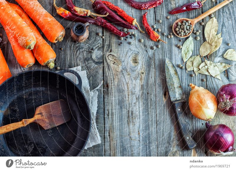 Empty black frying pan and vegetables Old Red Dish Eating Wood Food Gray Brown Orange Fresh Table Herbs and spices Kitchen Vegetable Knives Slice