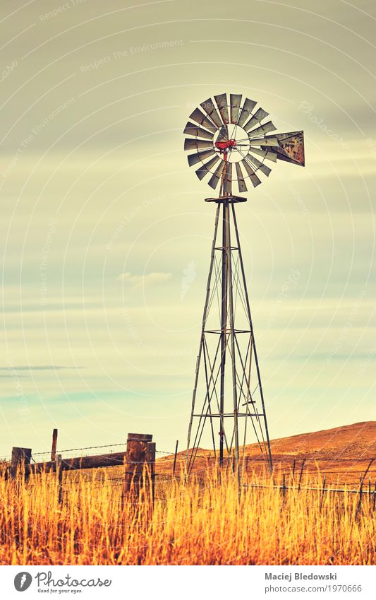 An old western windmill tower. Sky Old Autumn Grass Field Retro Wind USA Energy Symbols and metaphors Farm Rural Western Windmill Wild West Ranch